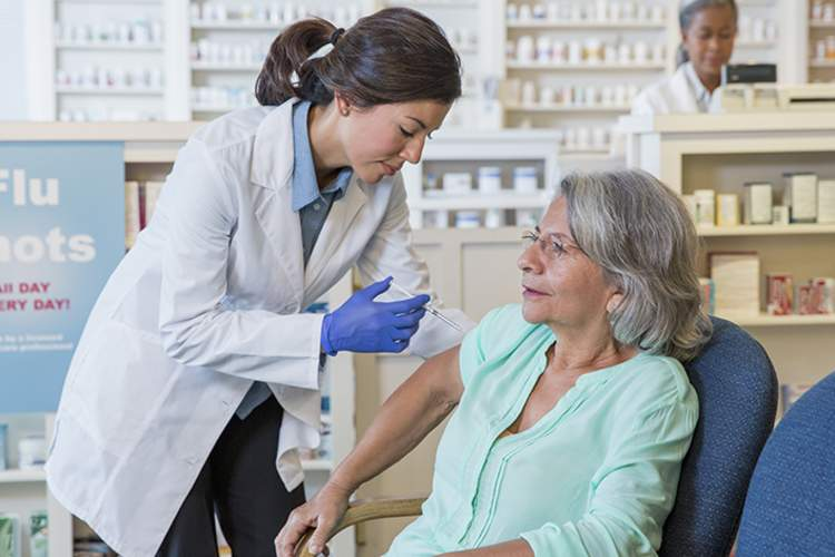 Senior woman receiving a flu shot at the pharmacy.