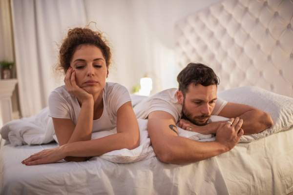 Depressed couple having relationship problems in their bed