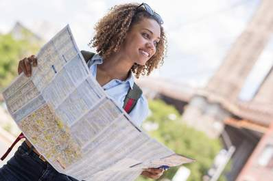 Healthy woman outside holding a map.