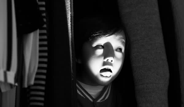 Child hiding in closet making scary faces.