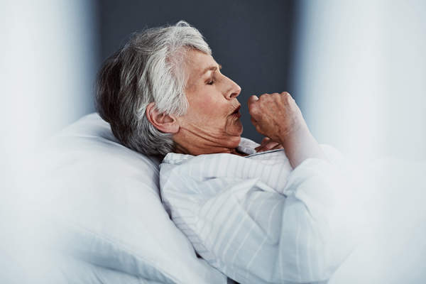 Senior woman coughing in bed