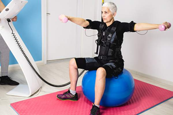 Senior woman exercising with a robotic suit.