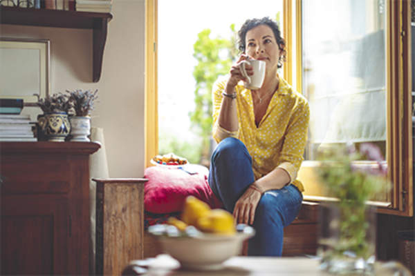 Woman relaxing and enjoying a cup of coffee at home.