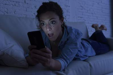 Woman lying on couch using mobile phone internet