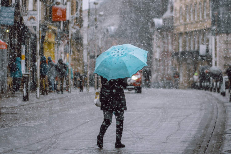 person with blue umbrella in snowstorm