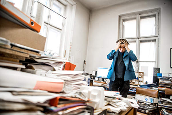 Man stressing about messy office.