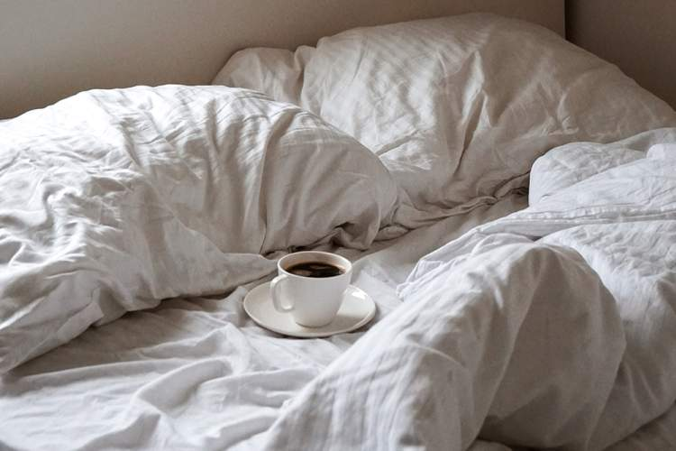 Cup of hot coffee on an unmade bed.
