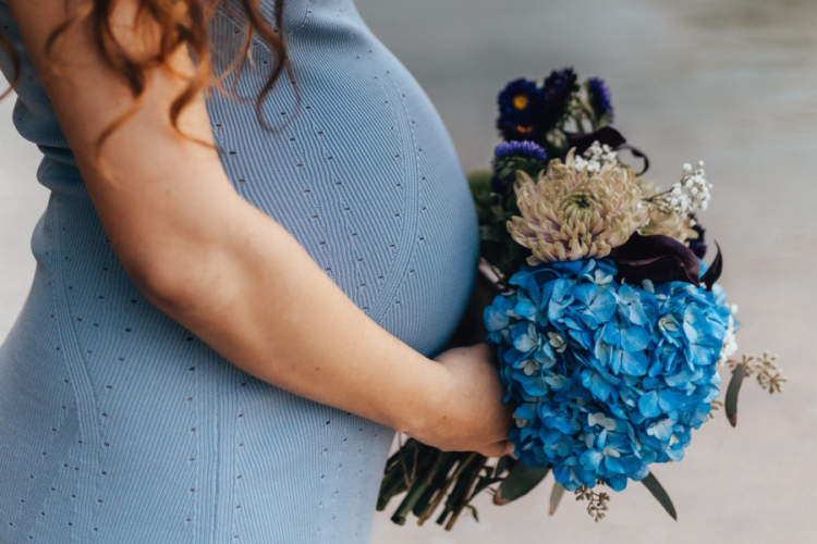 pregnant woman holding blue flowers