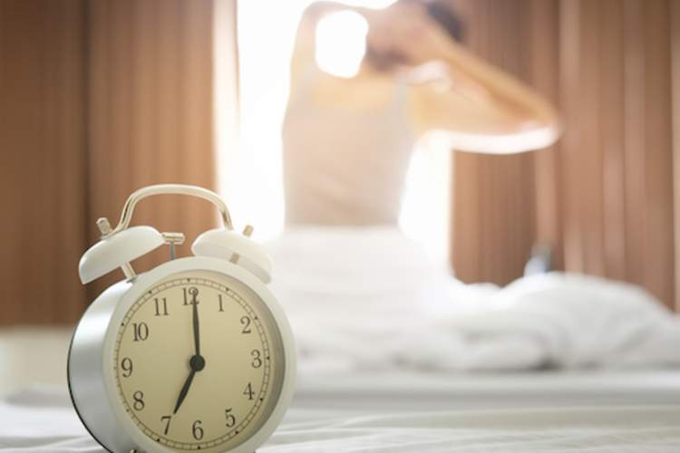 Alarm clock in foreground, woman rising from bed in background.