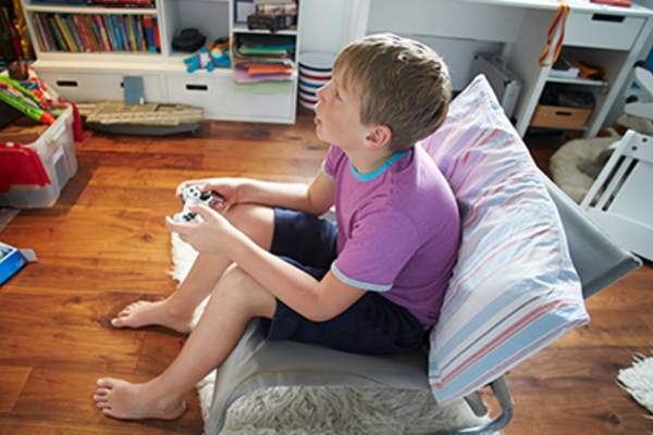 Young boy holding video game controller while playing games.