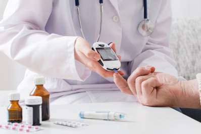 Doctor testing blood sugar with diabetes medications.