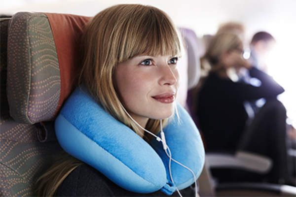 Smiling woman using neck pillow on plane.