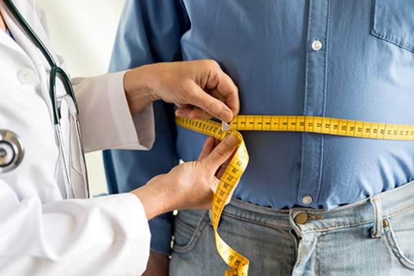 Doctor measuring an overweight man's waistline.