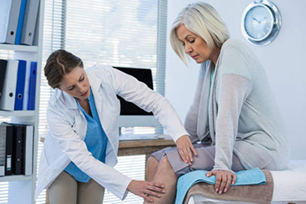 Middle age woman with osteoarthritis being seen by her doctor.