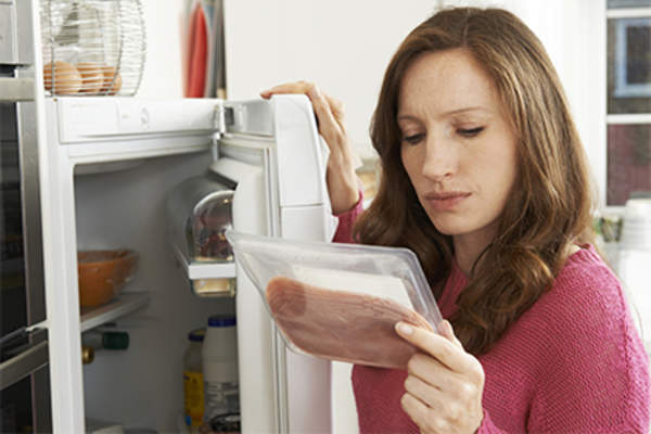 Woman taking meat out of the refridgerator.