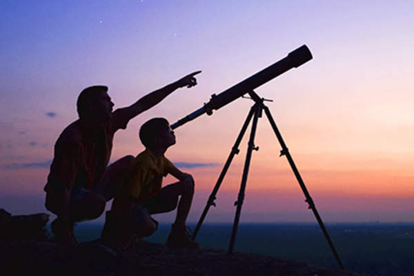 Father and son looking into a telescope.