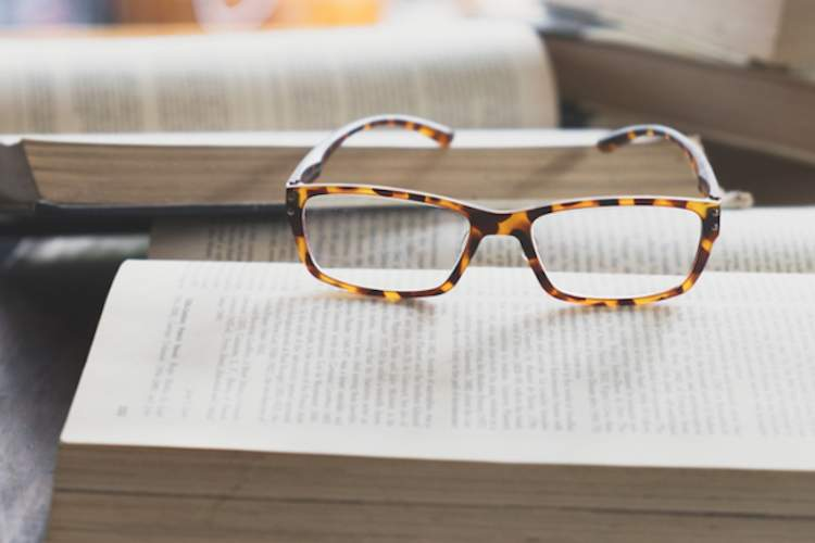 Eyeglasses on open book.
