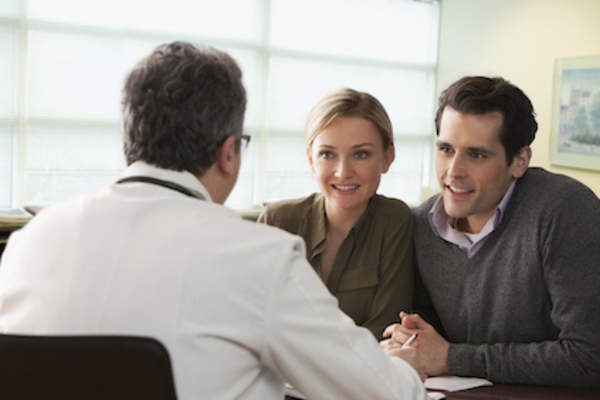 Young couple talking to fertility doctor.