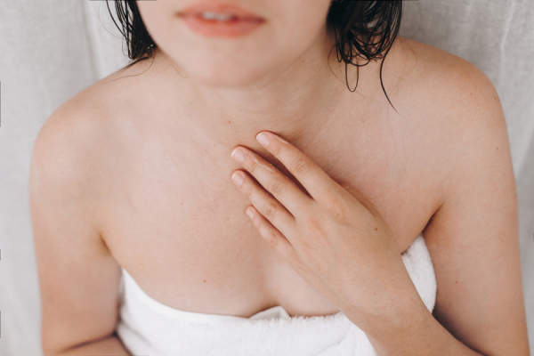 woman in towel touching chest