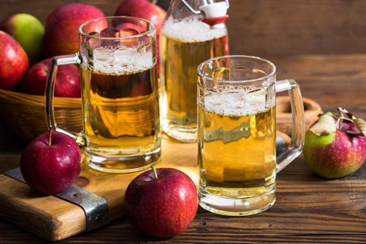 Apples and glasses of hard apple cider.