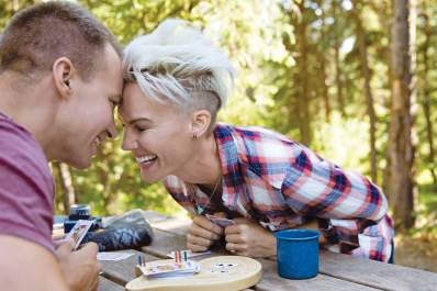 Man and woman playing cards on picnic table while camping.