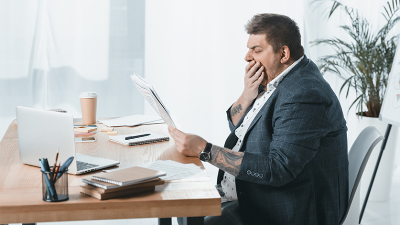 Overweight man yawning at his desk.