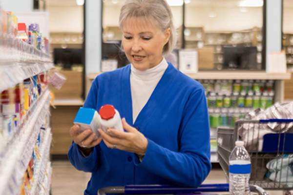 Senior woman looking at vitamin supplements.