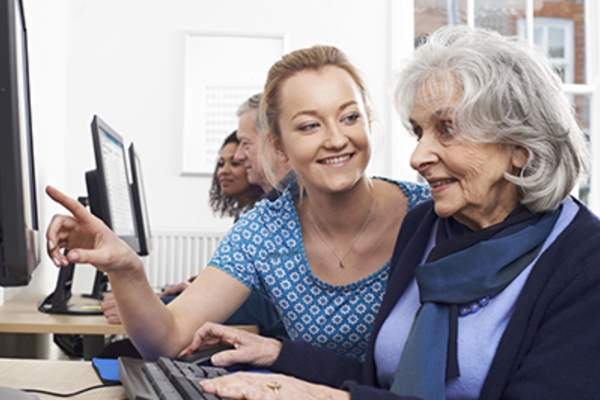 Woman helping senior woman on computer in center.
