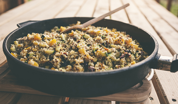 Autumnal quinoa salad with pumpkin and vegetables in a frying pan.