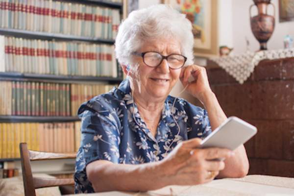 Senior woman listening to music on smartphone.