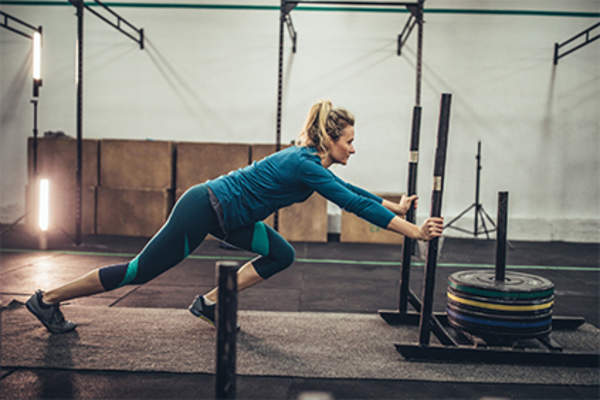 Woman pushing a weighted sled in the gym.
