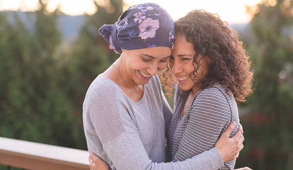 Woman hugging a friend with cancer.