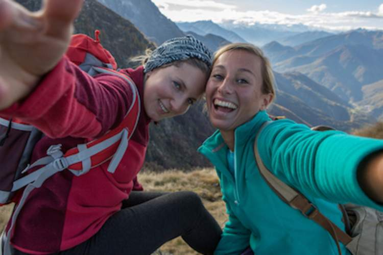 Girlfriends traveling together take a selfie on a mountaintop.