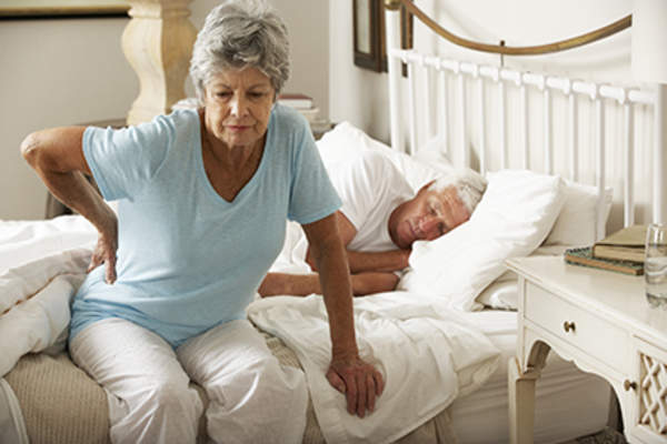 Senior woman experiencing back pain as she gets out of bed.