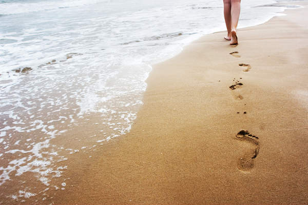 Woman leaving footprints behind on a beach