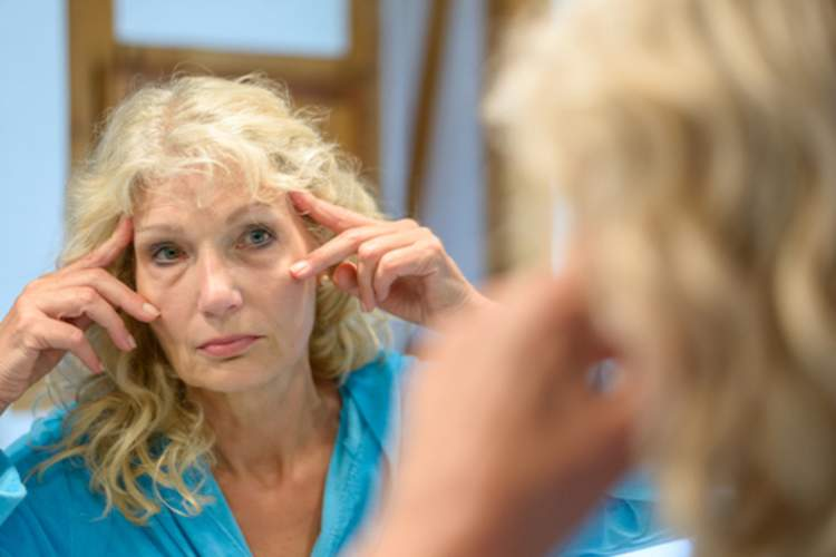 Woman stretching away wrinkles in mirror.