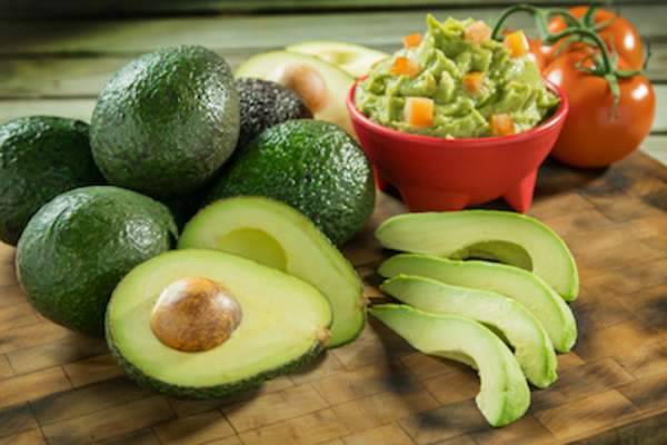 avocados and tomatoes on cutting board with bowl of fresh guacamole.