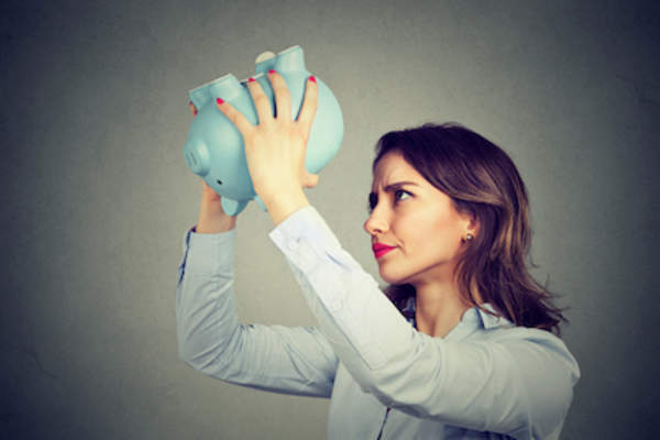 Woman shacking empty piggy-bank