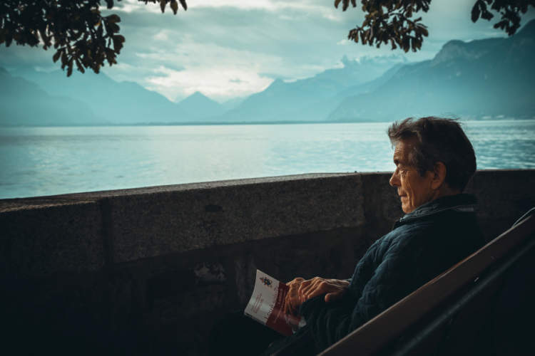 senior man sitting near lake, holding book