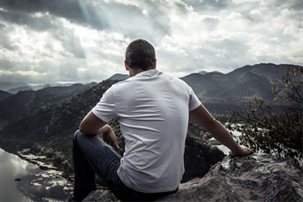 Man sitting on mountain peak looking out over a valley.
