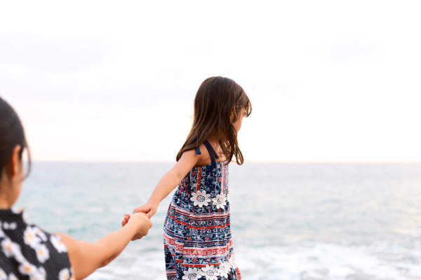 mother and daughter holding hands, daughter walking towards ocean