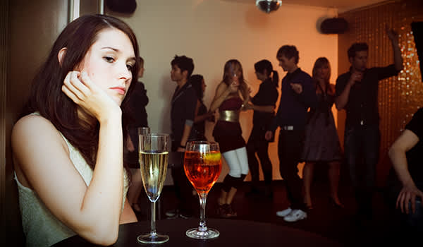 Young woman is sitting alone at a party