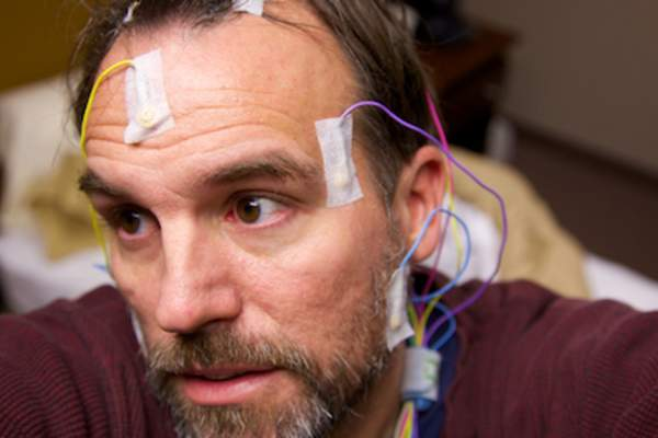 Man wired up to participate in sleep study.