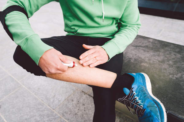 Man in workout clothes putting ointment on leg