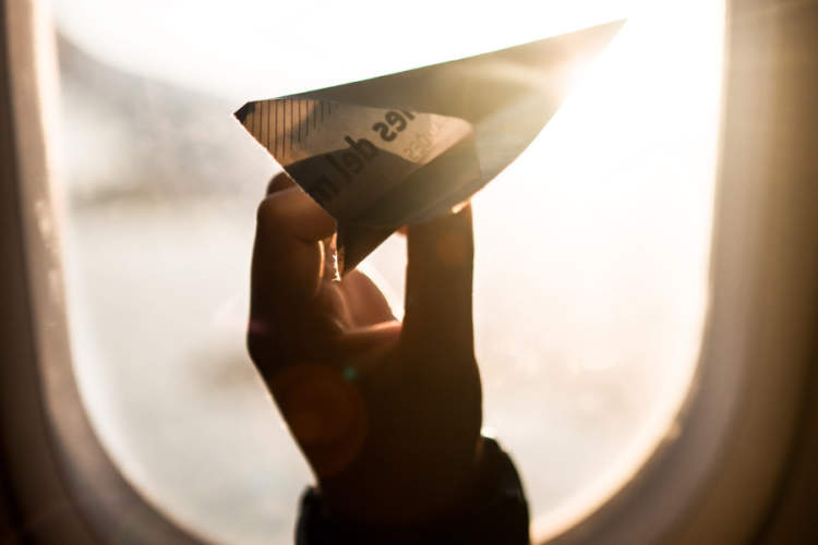 hand holding paper airplane in front of airplane window