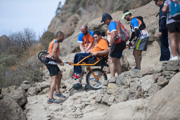 A group of people facilitating access to a person in a specialised mobility wheelchair in the mountains of the Parque Rural del Nublo.