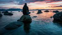man sitting on rock in water meditating