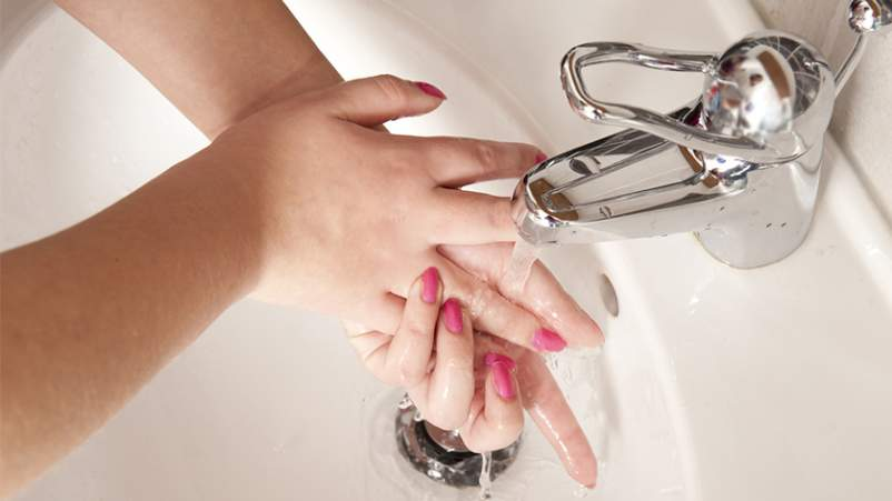 Woman washing hands with running water in the sink.