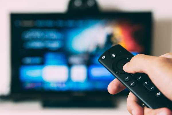 hand using remote on tv