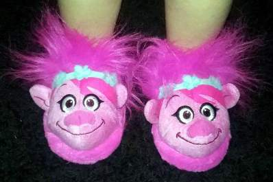 Little girl wearing troll slippers.